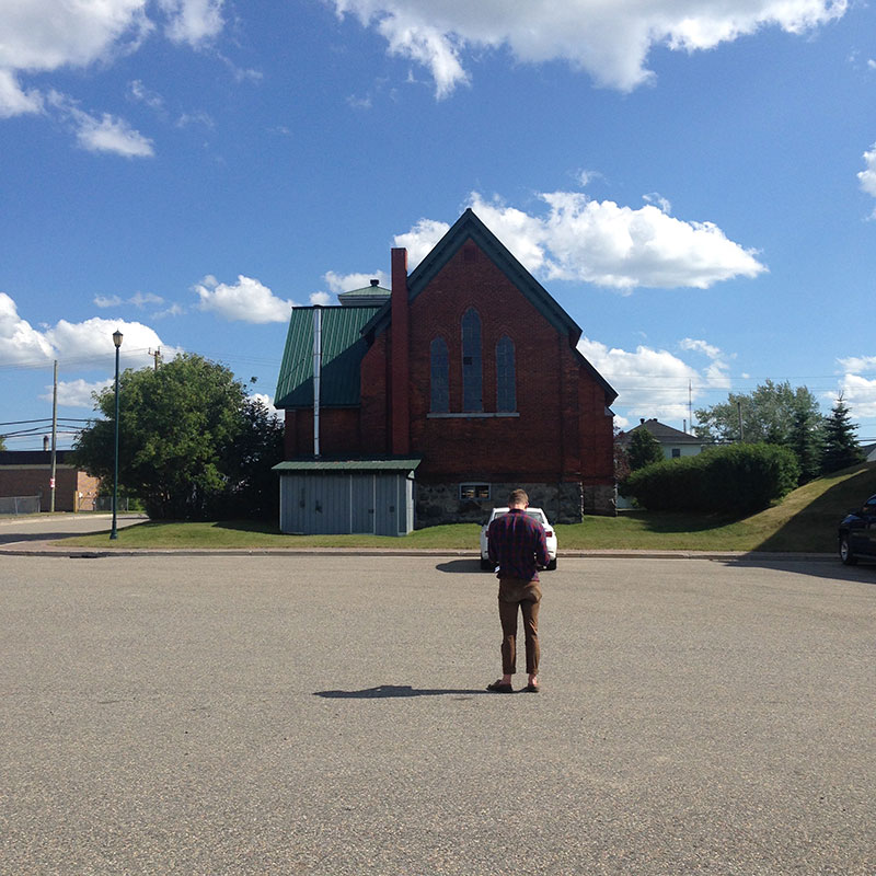 A man stands in an empty church parking lot looking at the church.