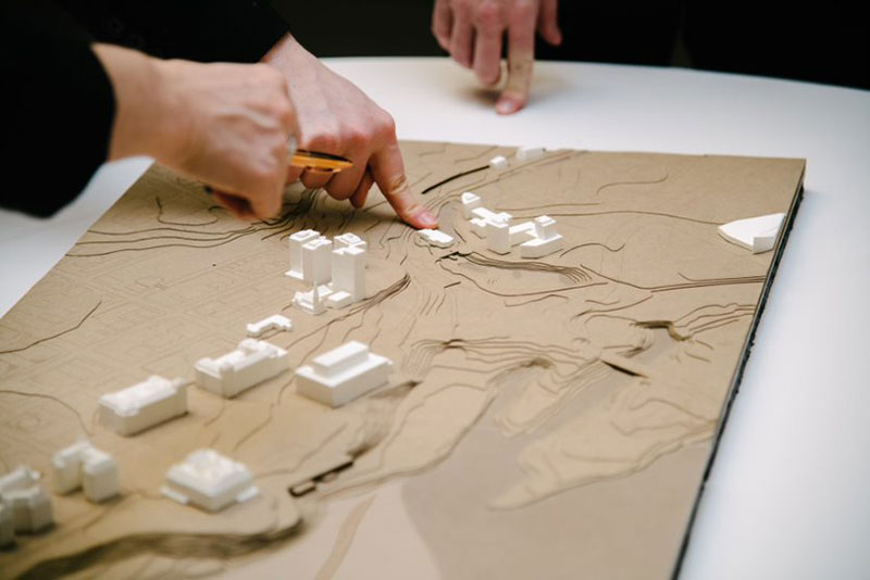 participants pointing at a topographical map of ottawa on table